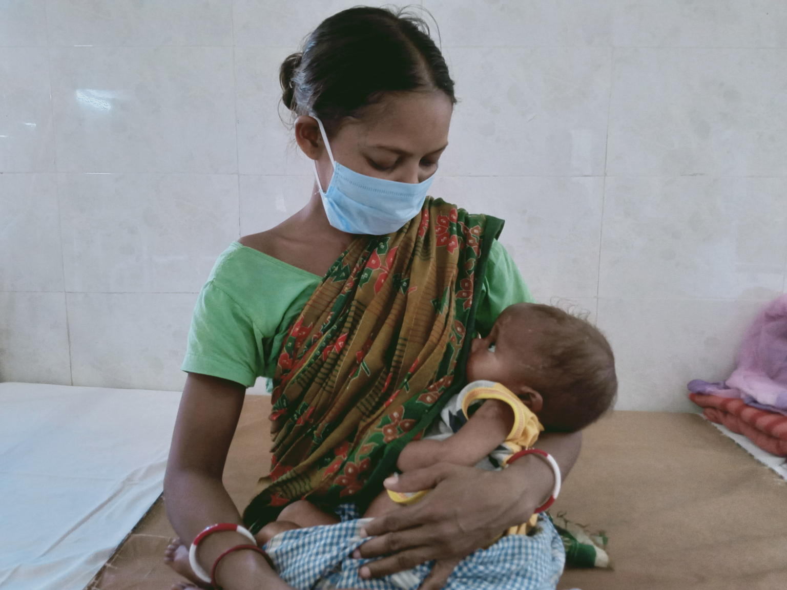 Mother in mask breastfeeding