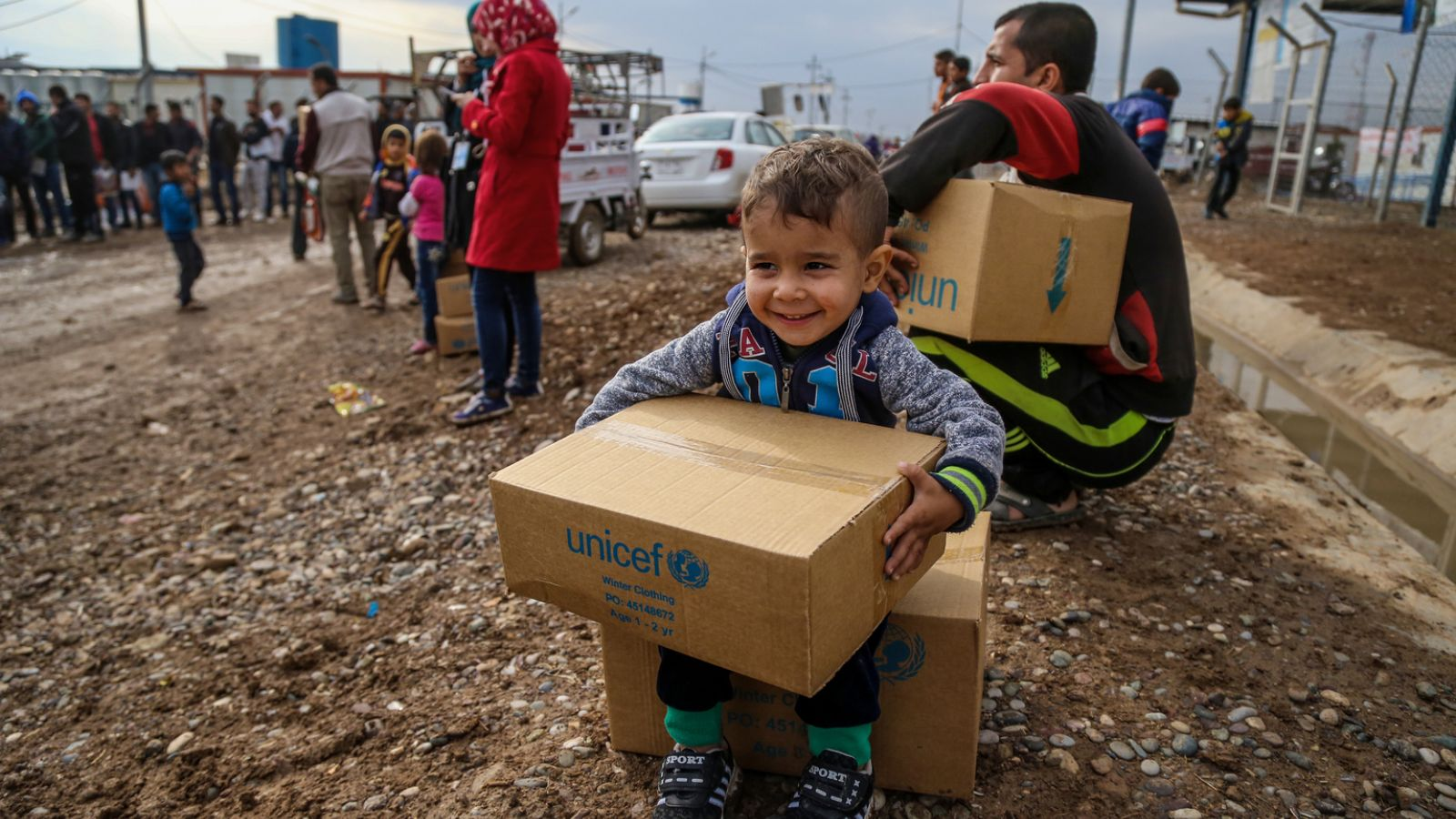 Rafi, 3, sits on a box of winter clothing that his family received from a distribution at Kawergosk Syrian Refugee Camp in Erbil Governorate in the Kurdistan Region of Iraq