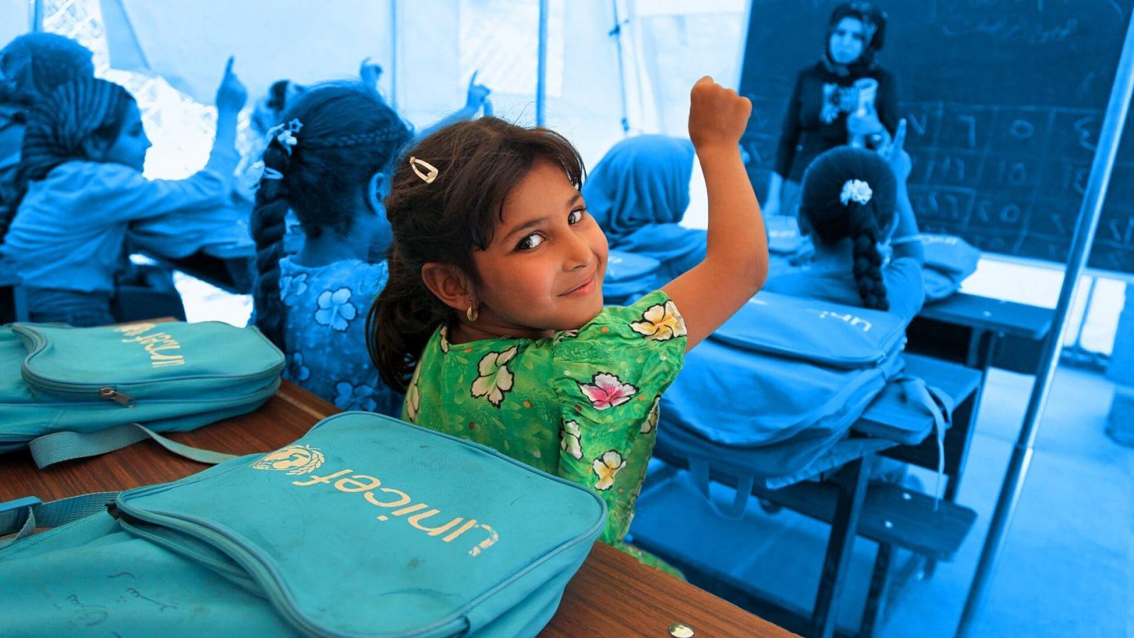 Girl raises her hand in UNICEF classroom.